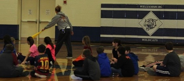 Students sitting on gym floor in gym class