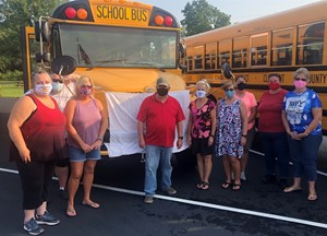 District bus drivers pictured in front of a school bus